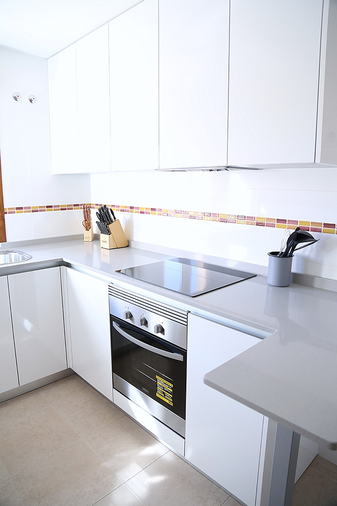 Diseño de cocinas en Cocina blanca pequeña con barra de desayuno en ...